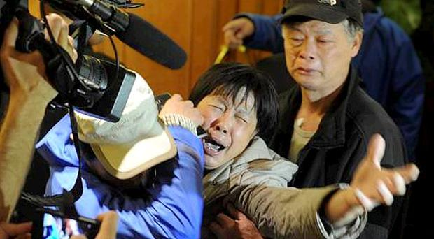 A family member of a passenger from the missing Malaysia Airlines flight MH370 reacts at Lido Hotel on March 24, 2014 in Beijing, China