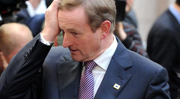 Irish Prime Minister Enda Kenny puts his hand on his head as he arrives for an EU summit in Brussels on Thursday, March 20, 2014. (AP Photo/Eric Vidal)
