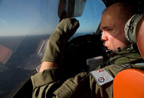 Flight Lt. Jayson Nichols shields his face from the sun as he looks out the cockpit of a Royal Australian Air Force AP-3C Orion aircraft during a search operation of the missing Malaysian Airlines flight MH370 over the southern Indian Ocean, Thursday, March 27, 2014. (AP Photo/Michael Martina, Pool)