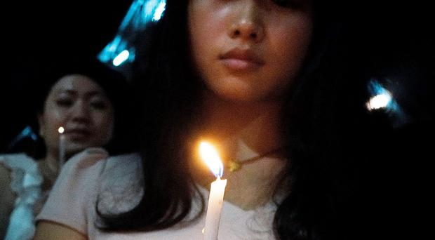 Woman holds candle during a candle light vigil to remember the victim of the ill-fated flight MH370