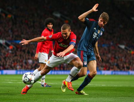 Nemanja Vidic of Manchester United and Thomas Mueller of Bayern Muenchen compete for the ball during the UEFA Champions League Quarter Final first leg