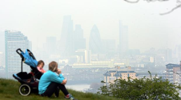 Dust particles and pollution from cars hangs over London, seen from Greenwich, as people suffering the effects of high levels of pollution - including sore eyes, coughs and sore throats - should cut down the amount of activity they take outside, experts have warned.