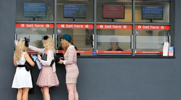 Racegoers place their bets during Ladies Day at the Crabbie's Grand National 2014 Festival at Aintree Racecourse, Liverpool. PRESS ASSOCIATION Photo. Picture date: Friday April 4, 2014. See PA story RACING Aintree. Photo credit should read: Pete Byrne/PA Wire