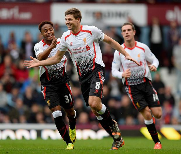 LONDON, ENGLAND - APRIL 06: Steven Gerrard (C)of Liverpool celebrates with teammate Raheem Sterling (L) after scoring the opening goal from the penalty spot during the Barclays Premier League match between West Ham United and Liverpool at Boleyn Ground on April 6, 2014 in London, England. (Photo by Mike Hewitt/Getty Images)