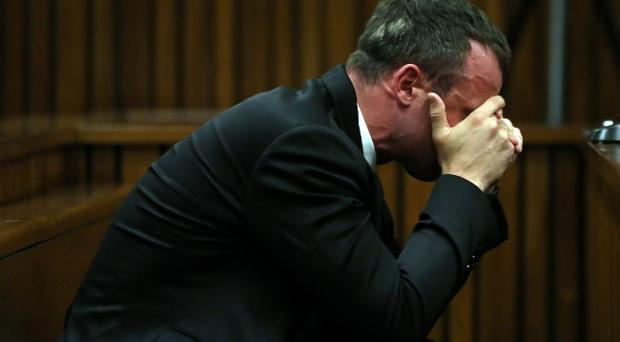 Oscar Pistorius reacts as he listens to evidence by a pathologist in court in Pretoria, South Africa, Monday, April 7, 2014. Pistorius is charged with murder for the shooting death of his girlfriend Reeva Steenkamp, on Valentines Day 2013. (AP Photo/Themba Hadebe, Pool)