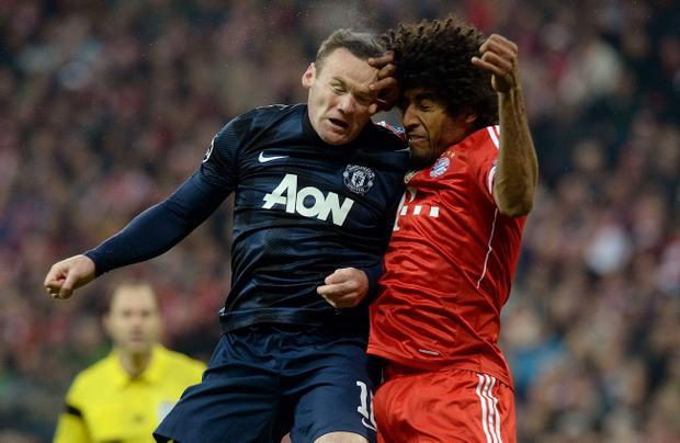 Manchester United's Wayne Rooney (left) and Bayern Munich's Dante collide in the air during the Champions League, Quarter Final, Second Leg at the Allianz Arena, Munich, Germany. PRESS ASSOCIATION Photo. Picture date: Wednesday April 9, 2014. See PA story SOCCER Bayern Munich. Photo credit should read: Martin Rickett/PA Wire