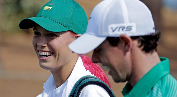Tennis player Caroline Wozniacki walks with Rory McIlroy during the par three competition at the Masters golf tournament Wednesday, April 9, 2014, in Augusta, Ga. (AP Photo/Darron Cummings)