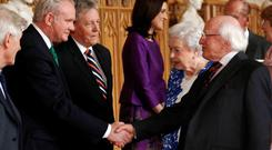Irish President Michael D Higgins (right) greets Northern Ireland's Deputy First Minister Martin McGuinness (left) and First Minister Peter Robinson (2nd left) with Queen Elizabeth II during a Northern Ireland-themed reception at Windsor Castle, during the first State visit to the UK by an Irish President. P