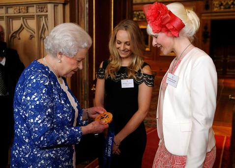 The Queen holds the gold medal of Paralympic skier Kelly Gallagher