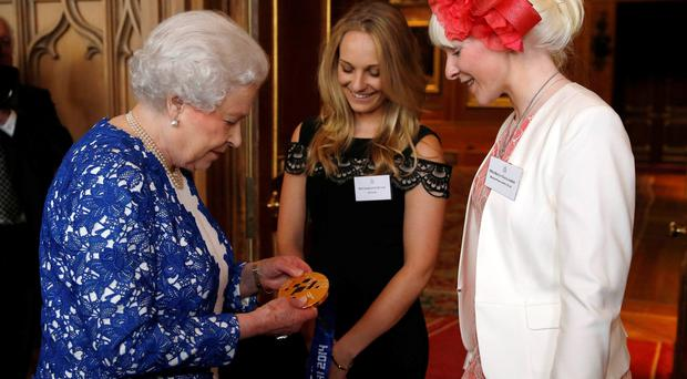 Queen holds the gold medal of Paralympic skier Kelly Gallagher (right) from Northern Ireland as her guide Charlotte Evans looks on during a Northern Ireland-themed reception at Windsor Castle, during the first State visit to the UK by an Irish President.