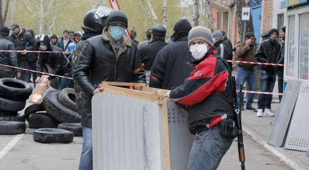 Armed pro-Russian men occupying the police station in the eastern Ukraine town of Slavyansk carry riot shields in Slavyansk, Saturday, April 12, 2014. Pro-Moscow protesters have seized a number of government buildings in the east over the past week, undermining the authority of the interim government in the capital, Kiev. (AP Photo/Efrem Lukatsky)