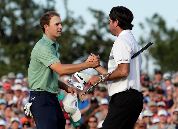 Bubba Watson, right, shakes hands with Jordan Spieth after winning the Masters golf tournament Sunday, April 13, 2014, in Augusta, Ga. (AP Photo/Charlie Riedel)