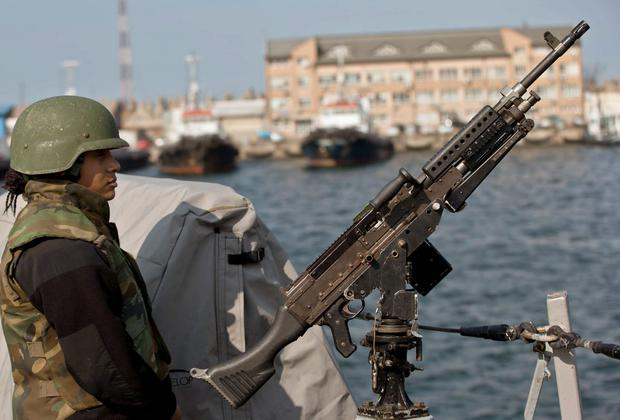 A US Navy sailor mans a gun on the deck of the USS Donald Cook, in the Black Sea port of Constanta, Romania, Monday, April 14, 2014. (AP Photo/Vadim Ghirda)