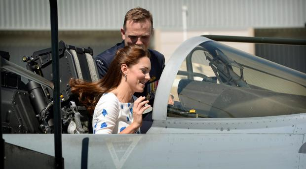 The Duke and Duchess of Cambridge sit in the cockpit of an F/A-18F Super Hornet during a visit to RAAF base Amberley during the thirteenth day of their official tour to New Zealand and Australia