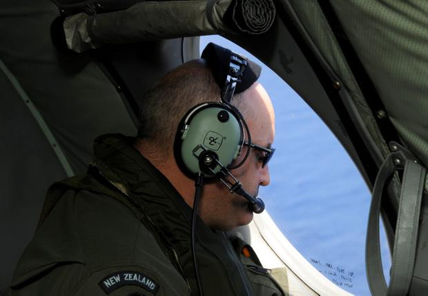 Flight Engineer Chris Poole of the Royal New Zealand Airforce (RNZAF) P-3K2-Orion aircraft, helps to look for objects during the search for missing Malaysia Airlines flight MH370 in flight over the Indian Ocean off the coast of Perth, Australia. (Photo by Greg Wood - Pool/Getty Images)