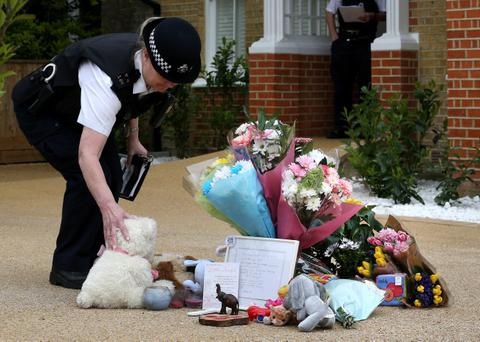 A policewoman stands a teddy bear up next to floral tributes placed in the drive of a house in New Malden where the bodies of three children were found on April 23, 2014 in south London, England. (Peter Macdiarmid/Getty Images)