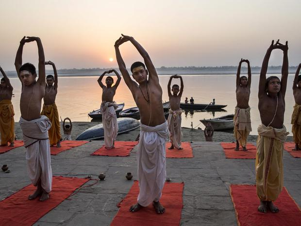 Young Indian Hindu Brahmins training to be priests perform yoga on a ghat on the Ganges River, holy to Hindus, at sunrise on April 23, 2014 in Varanasi, India. (Photo by Kevin Frayer/Getty Images)