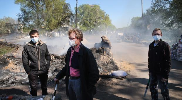 Pro-Russian activists guard a smoldering roadblock outside the village of Khrestyshche on April 24, 2014 near Slovyansk, Ukraine. (Photo by Scott Olson/Getty Images)