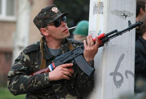 A pro-Russian gunman prepares his weapon as his comrades are about to storm a regional police station building in Luhansk, Ukraine, one of the largest cities in Ukraine's troubled east, Tuesday, April 29, 2014. (AP Photo)