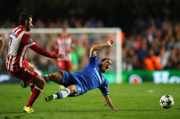 LONDON, ENGLAND - APRIL 30: Eden Hazard of Chelsea is tackled by Adrian Lopez of Club Atletico de Madrid during the UEFA Champions League semi-final second leg match between Chelsea and Club Atletico de Madrid at Stamford Bridge on April 30, 2014 in London, England. (Photo by Clive Rose/Getty Images)