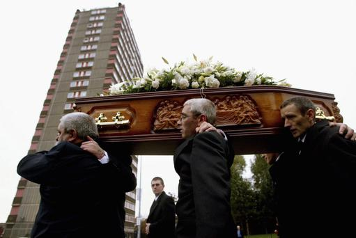 The sons of Jean McConville carry her remains to St Paul's church past Divis Flats on the Falls Road October 1, 2003 in West Belfast, Northern Ireland. (Photo by Getty Images)