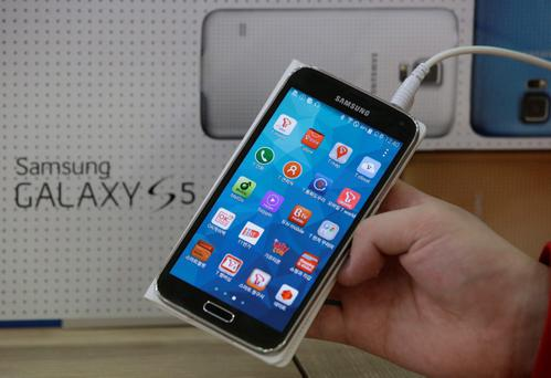 An employee shows Samsung's Galaxy S5 smartphone at a mobile phone shop in Seoul, South Korea. A California jury determined Friday May 2, 2014, that Samsung infringed Apple smartphone patents and awarded $120 million damages. (AP Photo/Lee Jin-man, File)