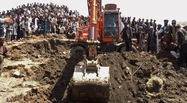Afghans search for survivors after a massive landslide landslide buried a village on Friday