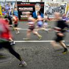 Runners pass the new Gerry Adams mural on the Falls Road