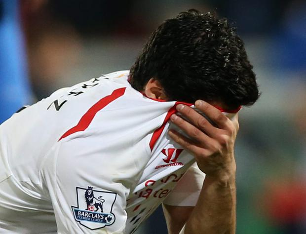 A dejected Luis Suarez, holds his shirt to his face following the end of the English Premier League soccer match (AP Photo/Alastair Grant)