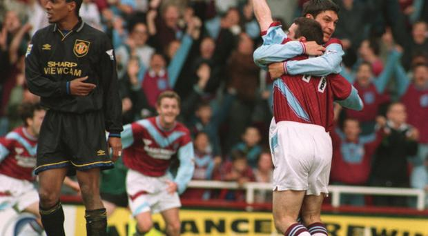 Hammer blow: A despondent Paul Ince looks away as Michael Hughes is congratulated by team-mate Trevor Morley after scoring the goal that cost Manchester United the League title