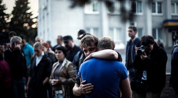 Two men react after Ukrainian national guardsmen opened fire on a crowd outside a town hall in Krasnoarmeisk, about 30 kilometers (20 miles) from the regional capital, Donetsk, Ukraine, Sunday, May 11, 2014. Although the voting in the Donetsk and Luhansk regions appeared mostly peaceful, Ukrainian national guardsmen opened fire on a crowd outside a town hall in Krasnoarmeisk, and an official with the regions insurgents said there were fatalities. (AP Photo/Manu Brabo)