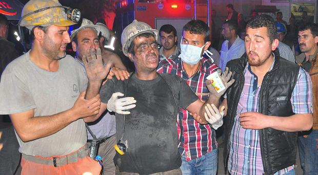 Miners escort a rescued friend after an explosion and fire at a coal mine in Soma, in western Turkey. An explosion and fire at a coal mine in western Turkey killed at least one miner Tuesday and left up to 300 workers trapped underground, a Turkish official said. Twenty people were rescued from the mine in the town of Soma in Manisa province but one later died in the hospital, Soma administrator Mehmet Bahattin Atci told reporters. The town is 250 kilometers (155 miles) south of Istanbul.