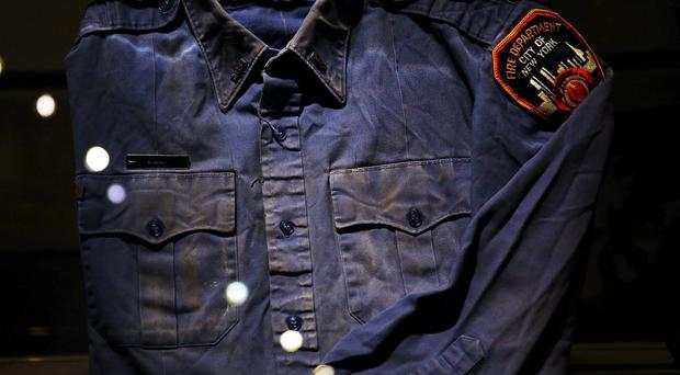 A firefighters shirt used at Ground Zero on September 11 is viewed during a tour the National September 11 Memorial Museum on May 14, 2014 in New York City. The long awaited museum will open to the public on May 21 following a six-day dedication period for 9/11 families, survivors, first responders, workers, and local city residents.