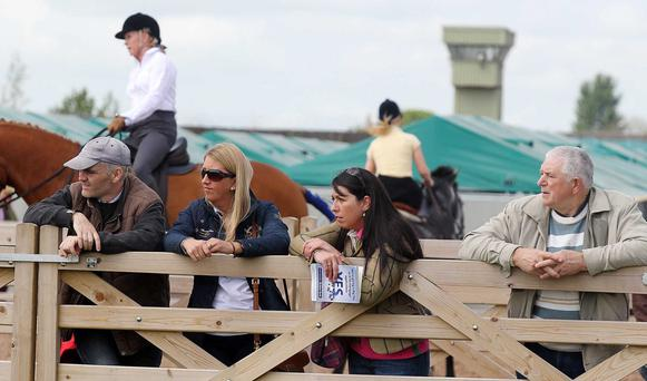 People watch the show jumping with an old watch tower from the Maze Prison in the background.
