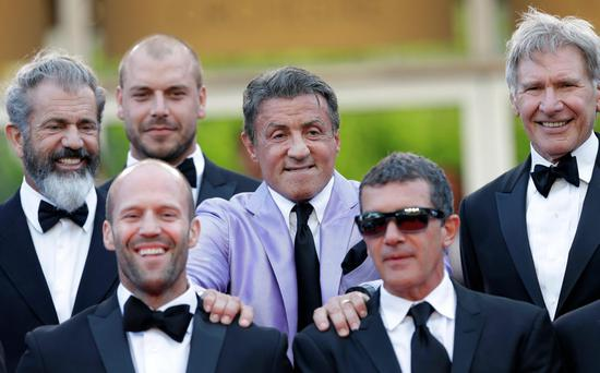 Actor Sylvester Stallone, center, puts his hands on the shoulders of Jason Statham, left, and Antonio Banderas, right, from the movie The Expendables 3, as they arrive for the screening of The Homesman at the 67th international film festival, Cannes, southern France, Sunday, May 18, 2014. (AP Photo/Thibault Camus)