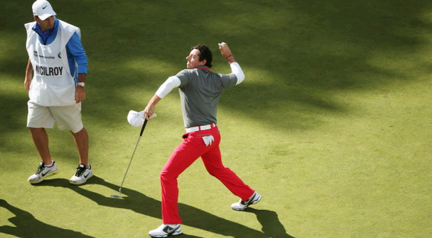 VIRGINIA WATER, ENGLAND - MAY 25: Rory McIlroy of Northern Ireland throws his ball to the crowd after holing a birdie putt on the 18th green during day four of the BMW PGA Championship at Wentworth on May 25, 2014 in Virginia Water, England. (Photo by Andrew Redington/Getty Images)
