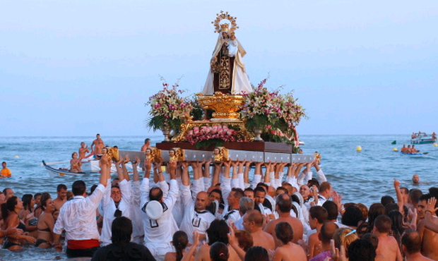 Water way to celebrate: Fishermen carry a statue of the Virgen del Carmen into the sea at Los Boliches to bless the year's catch - Los Boliches feature