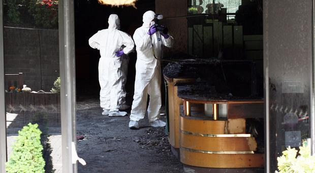 Forensic officers examine the charred reception at the Everglades Hotel in Derry yesterday