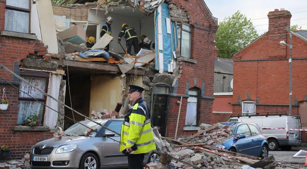 Emergency services at the scene in a suspected gas explosion on Sullivan Street. Pic Niall Carson/PA Wire