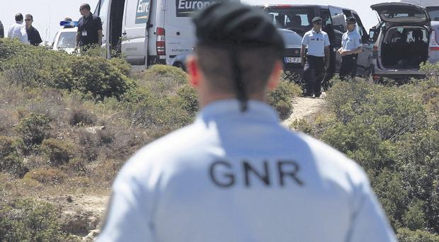 A Portuguese police officer stands guard at the site of a dig near Praia da Luz in the Algarve