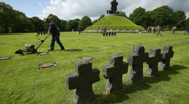 A groundskeeper mows grass among gravestones at the German Cemetery where approximately 21,000 German World War II soldiers are buried on June 5, 2014 at La Cambe, France. (Photo by Sean Gallup/Getty Images)