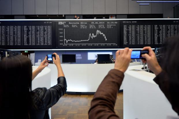FRANKFURT AM MAIN, GERMANY - JUNE 05: Two women take a picture of the index board that shows the DAX has broken the 10,000 mark for the first time ever at the Deutsche Boerse exchange on June 5, 2014 in Frankfurt, Germany. The rise comes after European Central Bank President Mario Draghi announced record low interest rates. (Photo by Thomas Lohnes/Getty Images)