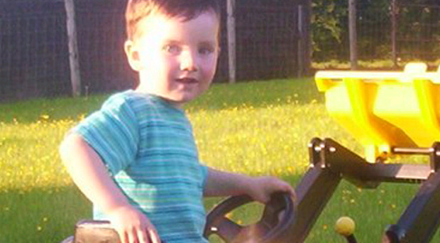 Robert Christie on his toy tractor at home