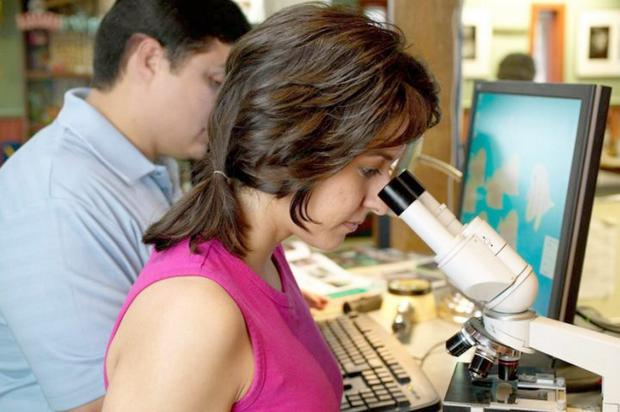 A woman looking in a microscope in a laboratory