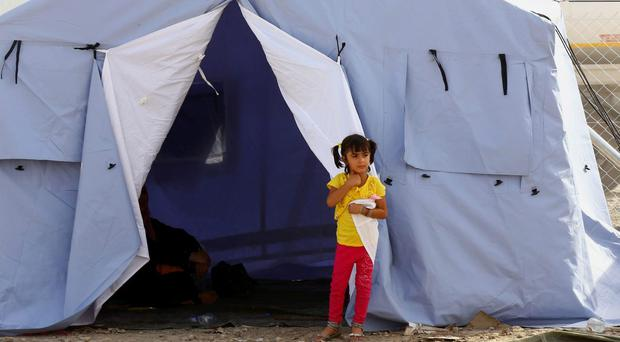 An Iraqi refugee girl from Mosul stands outside her family's tent at Khazir refugee camp outside Irbil, 217 miles (350 kilometers) north of Baghdad, Iraq, Wednesday, June. 11, 2014. (AP Photo)
