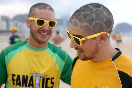 RIO DE JANEIRO, BRAZIL - JUNE 11: Two Australian football fans show off their football style haircuts at Copacabana beach on June 11, 2014 in Rio de Janeiro, Brazil. (Photo by Clive Rose/Getty Images)