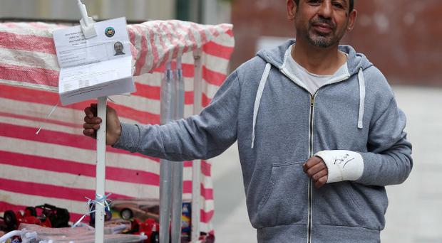 Trader Musa Gulusen, who was assaulted in a racist attack on Wednesday, pictured at his stall on Royal Avenue in Belfast city centre