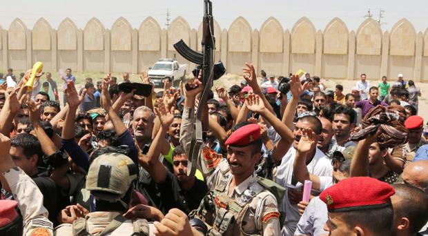 Iraqi Army soldiers and volunteers chant slogans against the al-Qaida inspired group Islamic State of Iraq and the Levant