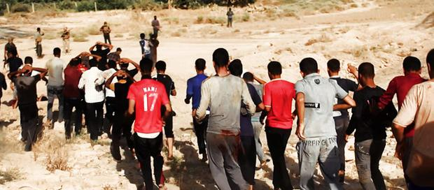 This image posted on a militant website on Saturday, June 14, 2014, which has been verified and is consistent with other AP reporting, appears to show militants from the al-Qaida-inspired Islamic State of Iraq and the Levant (ISIL) leading captured Iraqi soldiers wearing plain clothes to an open field moments before shooting them in Tikrit, Iraq. (AP Photo via militant website)