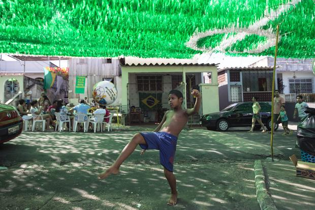 A boy plays football on Rua Santa Isabel which is covered with colourful streamers to celebrate the FIFA World Cup on June 15, 2014 in Manaus, Brazil